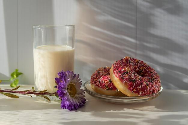 La colazione del mattino un bicchiere di latte e ciambelle fresche sotto un raggio di sole.