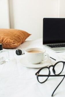 Colazione mattutina con caffè su lino bianco. moda donna, bellezza con laptop, cosmetici, accessori
