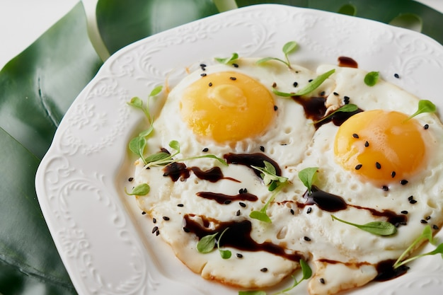 Colazione mattutina con uova fritte e foglia della pianta sul tavolo bianco