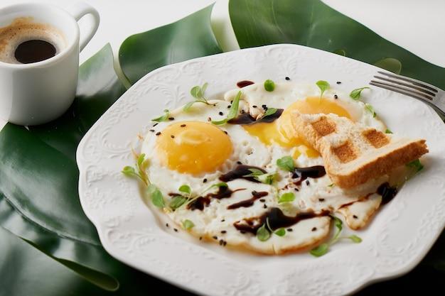 Colazione mattutina con uova fritte, pane tostato e caffè in tazza bianca e foglia di pianta sul tavolo bianco