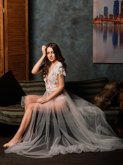 Mattina della sposa. ragazza sexy che posa in biancheria intima di pizzo bianco. ritratto di una bella giovane donna in una biancheria intima bianca. donna seducente in lino bianco e vestaglia.