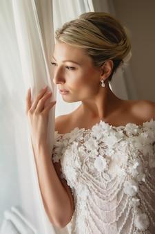 Mattina della sposa. femmina snella in abito da sposa alla finestra. la sposa guarda la luce. bella mattina di nozze. immagine diagonale. ragazza fantastica. la donna mostra le emozioni. bionda con gli occhi azzurri