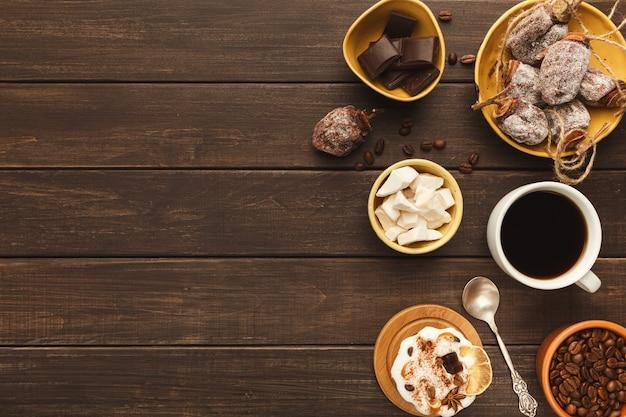 Priorità bassa del caffè del mattino. bordo della tazza di amaro americano, fagioli, cioccolato, cachi secco, piccola torta e zucchero raffinato su tavola in legno rustico, copia spazio, vista dall'alto