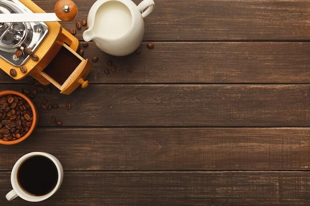 Priorità bassa del caffè del mattino. bordo della tazza di amaro americano, fagioli interi e macinati, barattolo di latte e macinino vintage su tavola in legno rustico, spazio copia, vista dall'alto