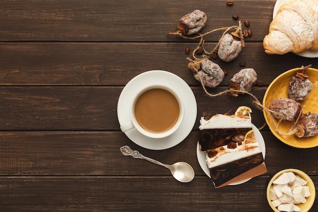 Priorità bassa del caffè del mattino. bordo della tazza di cappuccino, pezzi di torta, cachi secchi, croissant e zucchero raffinato su tavola in legno rustico, spazio copia, vista dall'alto