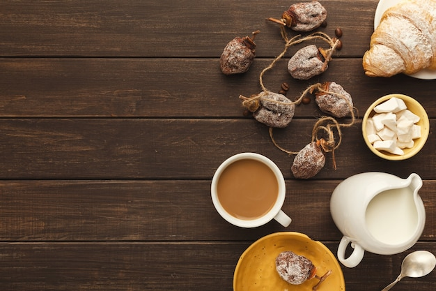 Priorità bassa del caffè del mattino. bordo della tazza di cappuccino, barattolo di latte, cachi secco, croissant e zucchero raffinato su tavola in legno rustico, spazio copia, vista dall'alto
