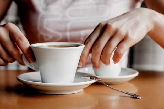 Caffè del mattino. primo piano delle mani delle donne con la tazza di caffè in un caffè.