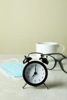 Concetto di caffè mattutino con sveglia, occhiali e maschera