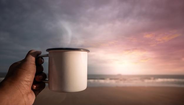Caffè del mattino. bere caffè caldo sulla spiaggia durante l'alba. mano che tiene una tazza per godersi la bevanda e la natura preferite. inizia un nuovo giorno. stile di vita rilassante e armonioso. vista pov