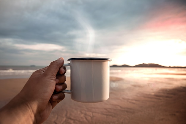 Caffè del mattino. bevendo caffè caldo sulla spiaggia durante l'alba.inizia un nuovo giorno. vista pov