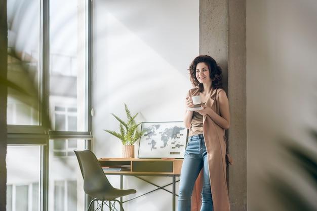 Caffè del mattino. giovane donna sorridente che mangia caffè al mattino