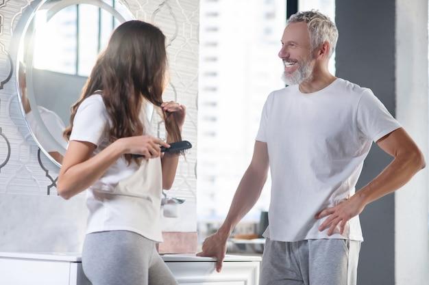 Buongiorno, comunicazione. gioioso uomo barbuto di profilo e donna dai capelli lunghi che pettina in piedi vicino allo specchio a casa comunicando