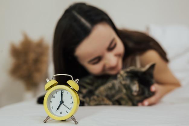 Concetto di mattina della ragazza che abbraccia il suo gatto focus sulla sveglia gialla