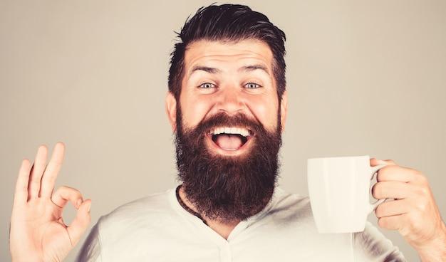 Concetto di mattina. l'uomo barbuto bello tiene una tazza di caffè, tè. buongiorno