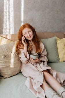 Conversazione mattutina della ragazza dai capelli rossi al telefono durante la colazione, che ha portato con sé a letto.