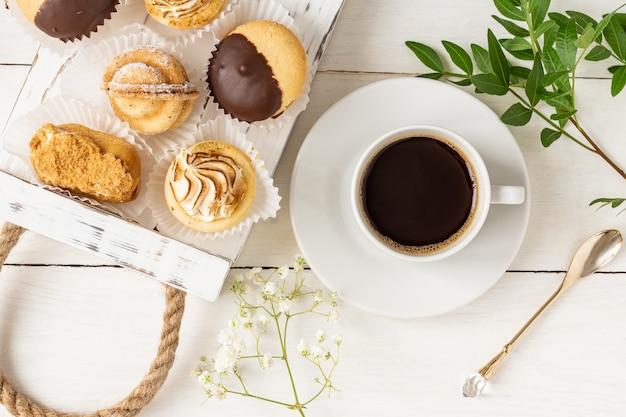 Tazza di caffè mattutina con gustosi dessert appena sfornati decorati con foglie e fiori.