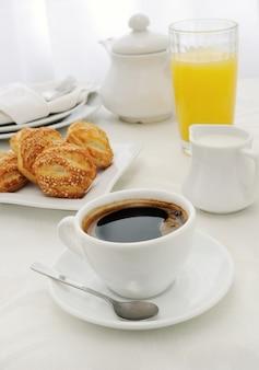Mattina tazza di caffè con panini appena sfornati con semi di sesamo, succo di frutta e latte