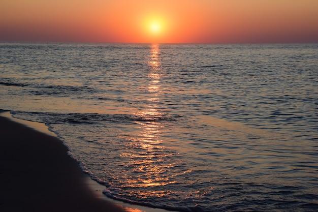 Sole mattutino dell'alba sullo sfondo della spiaggia sabbiosa del mare, con riflessi sulle onde calme