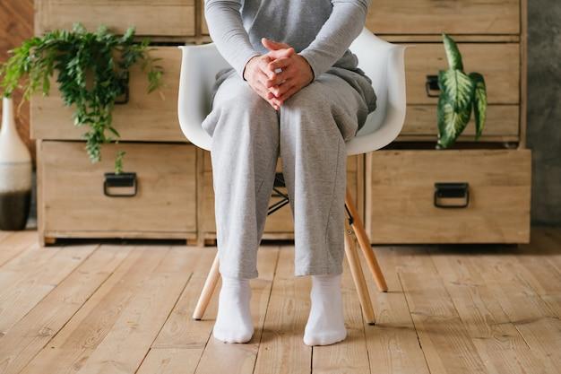 Dubbi mattutini. uomo in pigiama seduto sulla sedia in punta di piedi e con le mani a guglia.