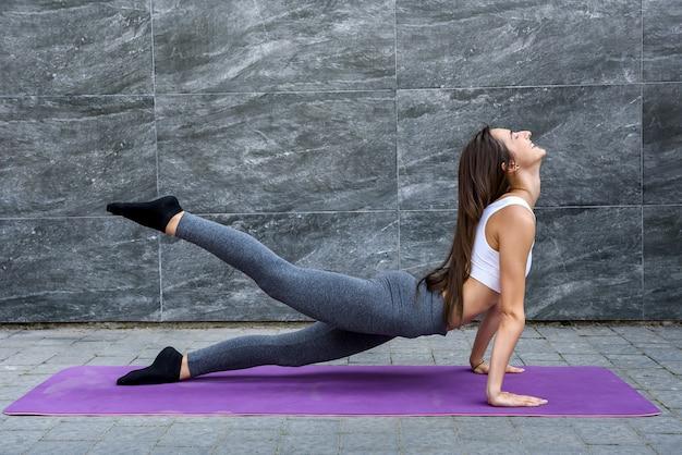 Esercizi mattutini all'aperto. giovane donna che si allena sul tappetino all'aperto in città