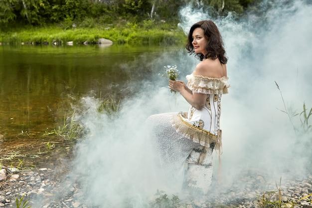 Nebbia mattutina sulla riva di un fiume nella foresta e una giovane donna vestita con un abito con un corsetto tiene in mano un mazzo di fiori di campo.