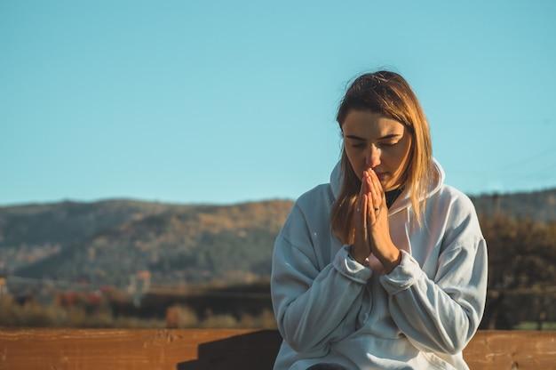 Al mattino la ragazza chiuse gli occhi, pregando all'aperto, le mani giunte nel concetto di preghiera per la fede, la spiritualità e la religione. pace, speranza, concetto di sogni.