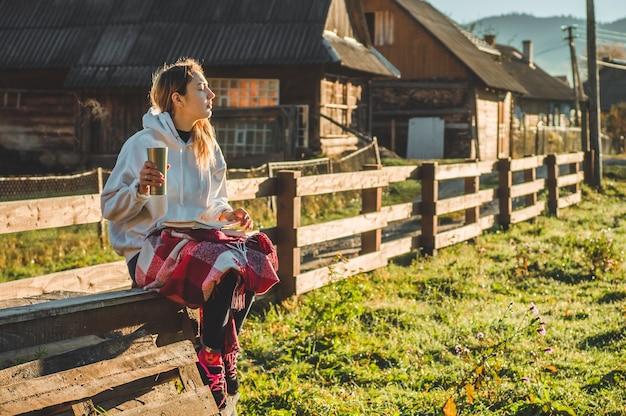 Al mattino la ragazza si siede su una panca di legno in mezzo alla natura, legge un libro e beve tè caldo da una tazza termica. concetti lettura in natura. formazione all'aperto