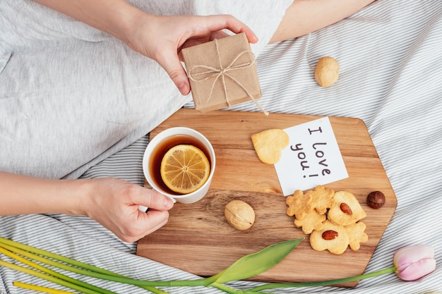 Saluto mattutino della tua ragazza preferita. colazione, fiori e un regalo a letto. congratulazioni per san valentino il 14 febbraio.