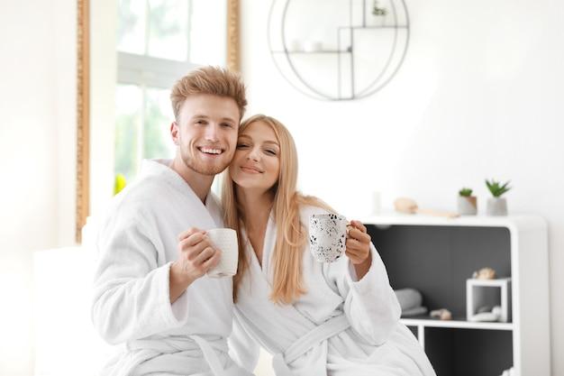 Mattina di giovani coppie felici in accappatoi che bevono caffè a casa