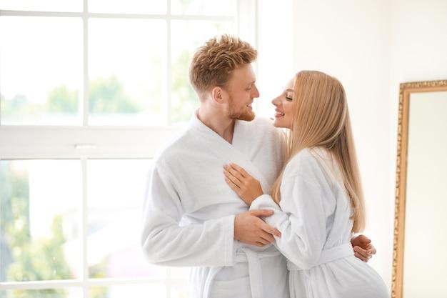 Mattina di giovane coppia felice in accappatoi a casa