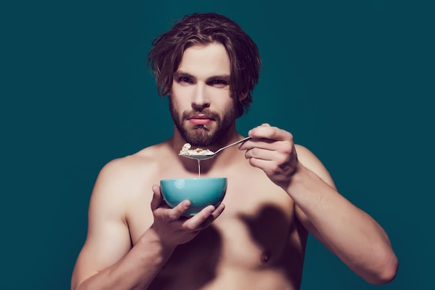 Mattina cibo sano e dieta, uomo con petto nudo mangiare farina d'avena. cereali per la colazione, cibo sano per uomo o atleta sportivo.