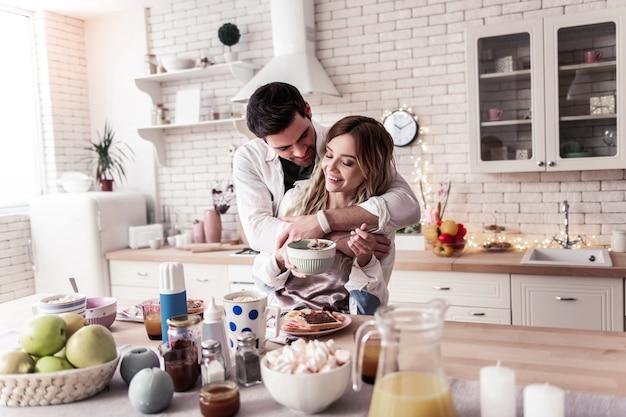 Abbracci mattutini. giovane donna dai capelli lunghi che indossa una camicia bianca e il suo bel marito dai capelli scuri in piedi in cucina