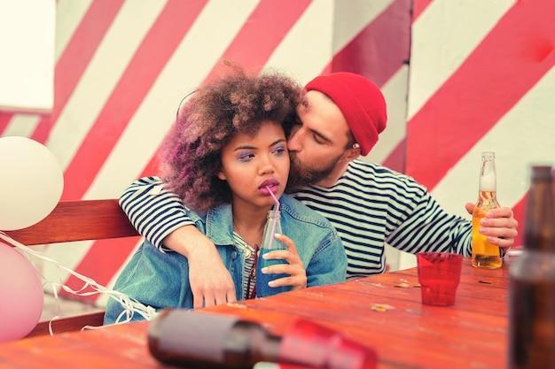 Bacio del mattino. giovane stanco che bacia la sua ragazza assonnata mentre era seduto al tavolo dopo la festa notturna con lei Foto Premium
