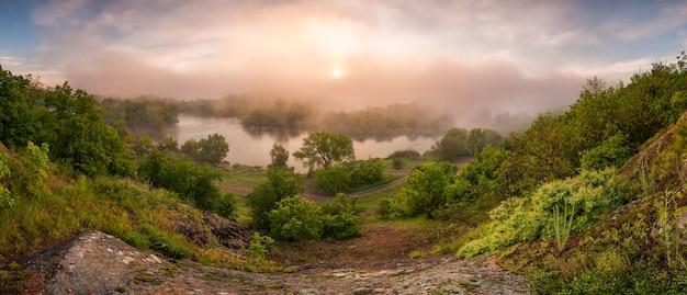 Paesaggio di mattina che sorge sopra il sole di nebbia del fiume