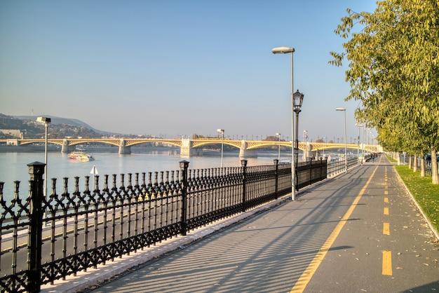 Paesaggio mattutino con vista sul marciapiede lungo il fiume danubio con vista sul ponte margherita a budapest, ungheria su uno sfondo di cielo azzurro.