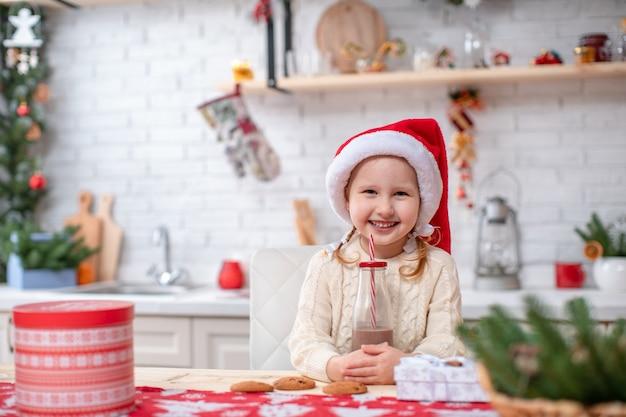 Al mattino, una bambina beve latte di cacao, seduta al tavolo della cucina.