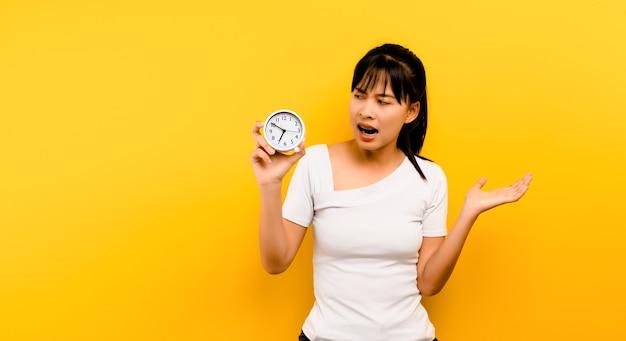 Orologio di piantagione mattutina donna asiatica che tiene la sveglia e sorride violentemente al suono dell'orologio.