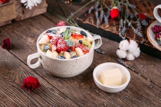 Mattina colazione a base di porridge con frutti di bosco dolci e burro
