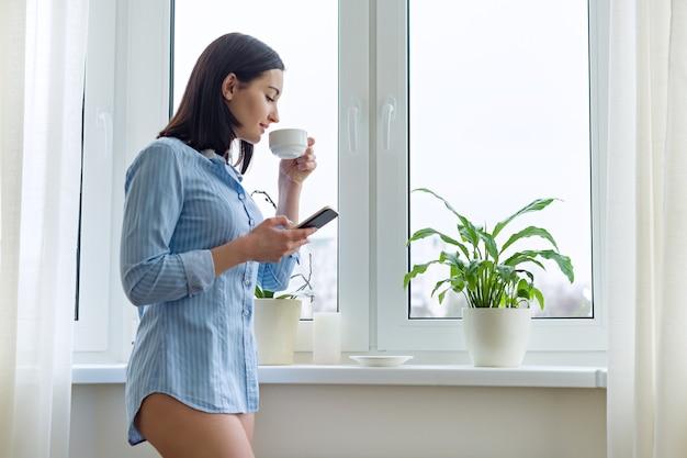 Ritratto di mattina di giovane donna sorridente in camicia a casa vicino alla finestra con testo di lettura dello smartphone
