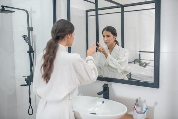 Procedure mattutine. una foto di una giovane donna in accappatoio in bagno