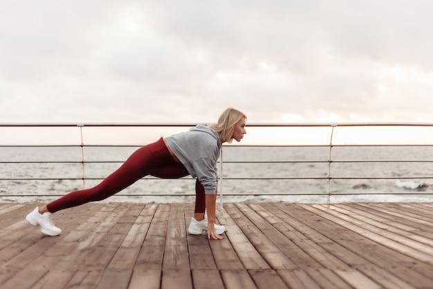 Corsa mattutina giovane donna atletica in abbigliamento sportivo pronta a correre sulla spiaggia all'alba