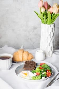 Decorazione della tavola di primavera mattutina. insalata in piatto, uova, tazza di caffè e croissant, tulipani freschi in vaso su sfondo bianco pulito della tovaglia. regolazione del posto del tavolo della colazione in colore bianco.