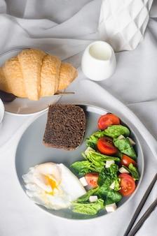 Decorazione della tavola di primavera mattutina. insalata in piatto, uova, tazza di caffè e croissant,