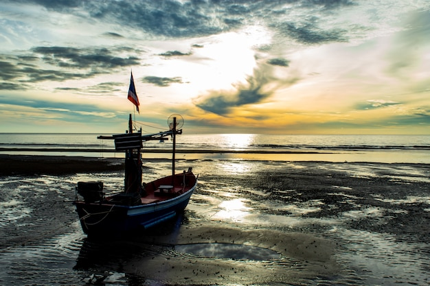 La luce del sole del mattino nel mare e la barca sulla spiaggia.