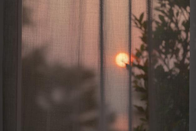 Alba mattutina dietro una tenda bianca e una finestra di vetro