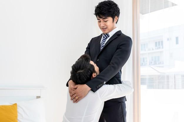 Al mattino dolce momento d'amore. coppia omosessuale asiatica abbraccia il marito prima del lavoro