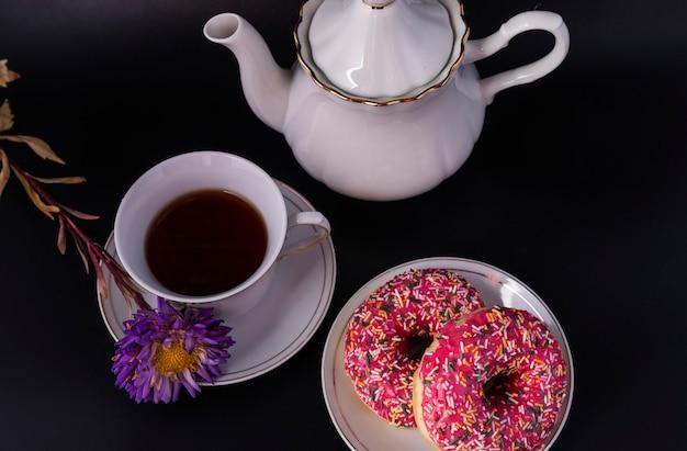 Tè del mattino e ciambelle fresche con glassa colorata su uno sfondo scuro vista dall'alto.