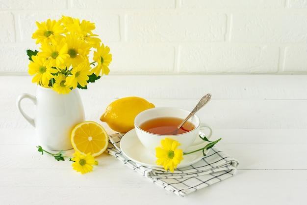 Tè del mattino con fiori di crisantemo giallo e limone.