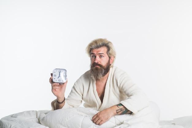 L'ora del mattino si sveglia uomo con la sveglia uomo barbuto a letto sveglia di routine mattutina