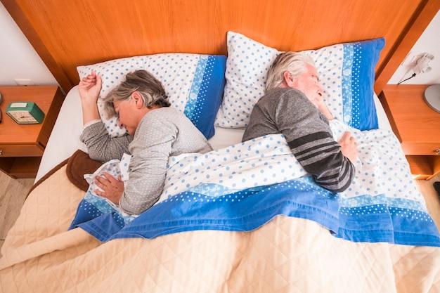 Sveglia al mattino per la coppia senior adulta a casa nel letto